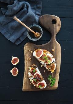 Sanduíches com ricota, figos frescos, nozes e mel na placa de madeira rústica