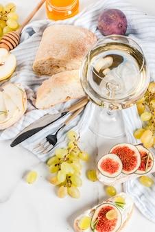 Sanduíches com ricota ou creme de queijo, ciabatta, figos frescos, peras, uvas, nozes e mel na mesa de mesa de mármore branco, com copo de vinho