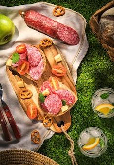 Sanduíches com salame. piquenique na grama.