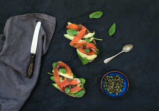 Sanduíches com salmão defumado, abacate, espinafre, alcaparra e manjericão sobre pedra ardósia escura.