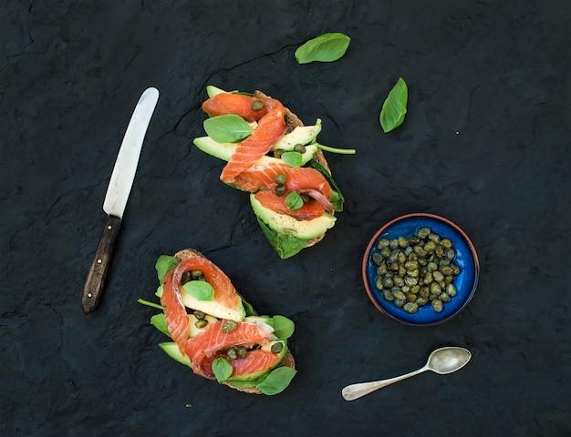 Sanduíches com salmão defumado, abacate, espinafre, alcaparra e manjericão