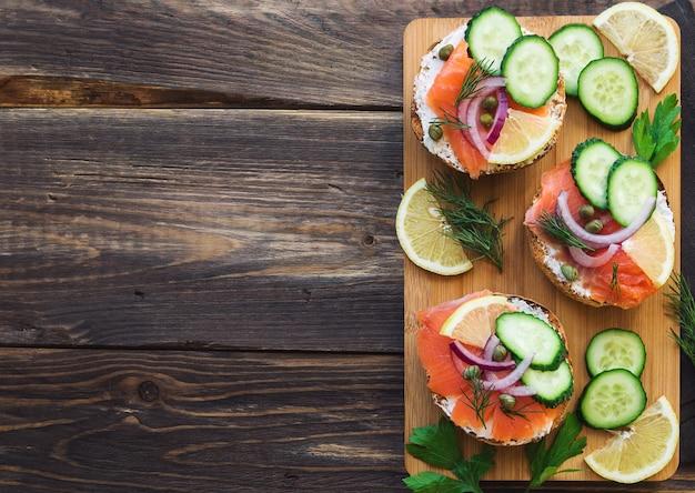 Sanduíches com salmão defumado, cebola roxa, alcaparras, pepino e limão em madeira rústica.
