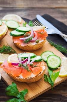 Sanduíches com salmão defumado, cebola roxa, alcaparras, pepino e limão em madeira rústica