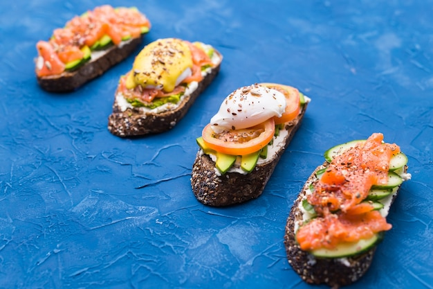 Sanduíches com salmão defumado, ovos, molho e abacate na superfície azul. conceito de café da manhã e