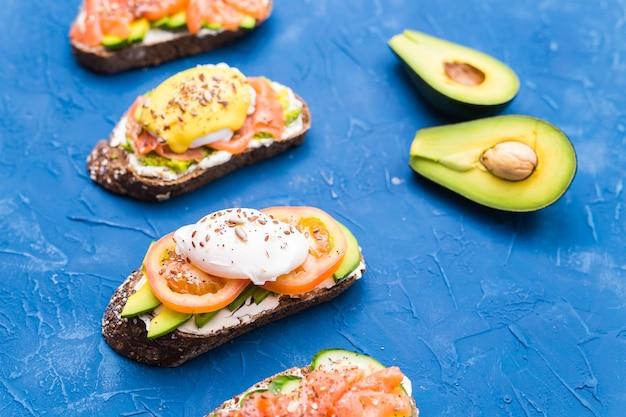 Sanduíches com salmão defumado, ovos, molho e abacate sobre fundo azul. conceito de café da manhã e