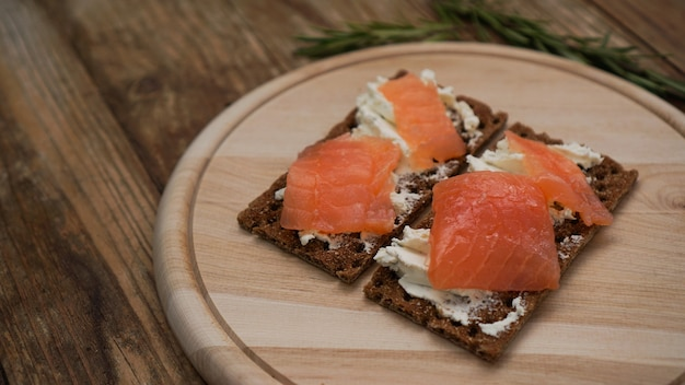 Sanduíches com salmão na tábua de madeira, vista de perto