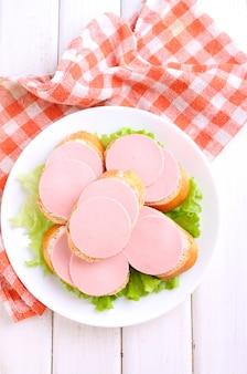 Sanduíches com salsicha doutoral em um prato branco sobre um fundo branco