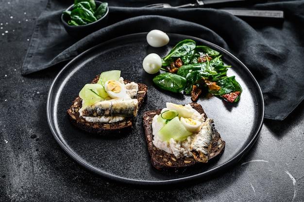 Sanduíches com sardinha, ovo, pepino e cream cheese, enfeite de salada com espinafre e tomate seco.