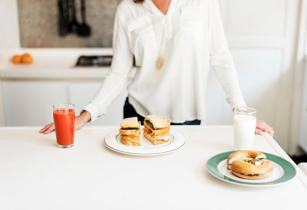 Sanduíches com suco e leite na mesa branca na cozinha