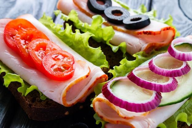 Sanduíches com tomates pique azeitonas e cebola vermelha
