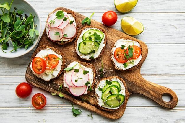 Sanduíches com vegetais saudáveis e micro-verduras em uma mesa de madeira