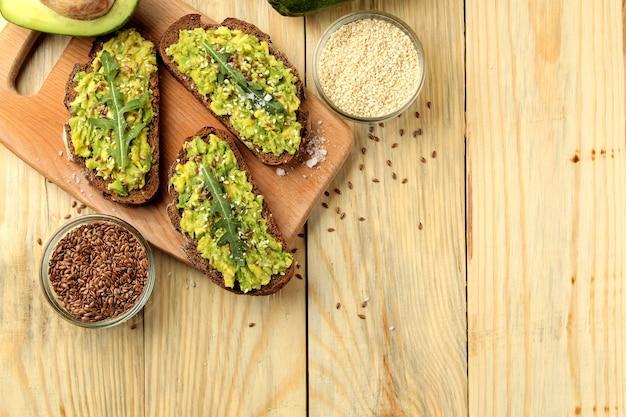 Sanduíches de abacate e rúcula e outros ingredientes em uma mesa de madeira natural. sanduíche com purê de abacate. vista de cima. com espaço para texto
