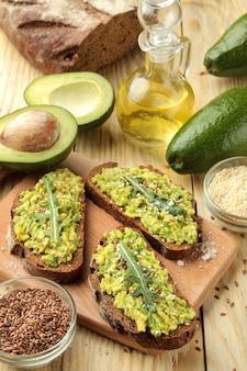 Sanduíches de abacate e rúcula e outros ingredientes em uma mesa de madeira natural. sanduíche com purê de abacate.