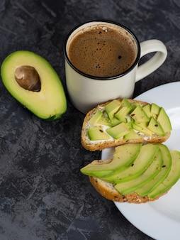 Sanduíches de abacate e uma xícara de café no café da manhã