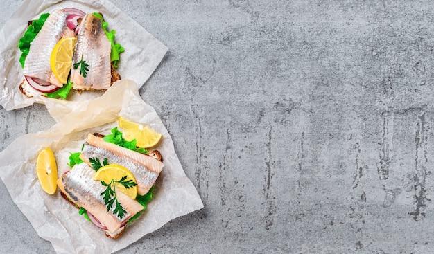Sanduíches de arenque, cebola e ervas em folha de papel, camada plana. conceito de lanche ou fast food, tradicional sanduíche smorrebrod. copie o espaço na mesa de pedra