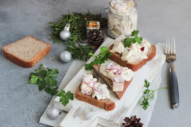 Sanduíches de arenque com cebola roxa, maçã, mostarda e salsa