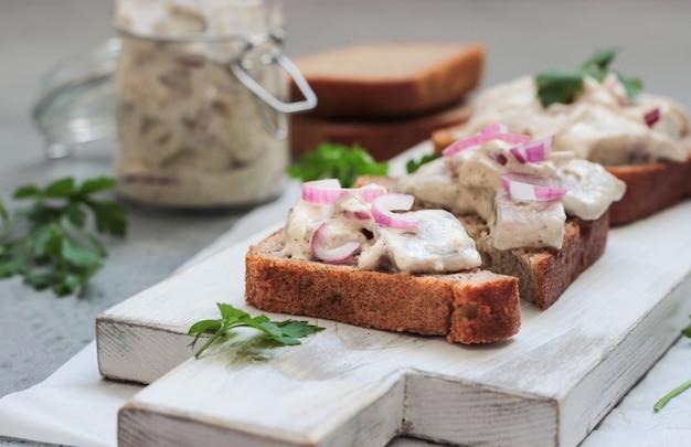Sanduíches de arenque com cebola roxa, maçã, mostarda e salsa.