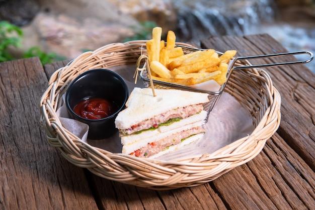 Sanduíches de atum servidos com batatas fritas e ketchup, dispostos em uma bela cesta de vime, colocada sobre uma mesa de madeira.