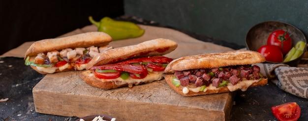Sanduíches de baguete com frango, carne, linguiça e legumes