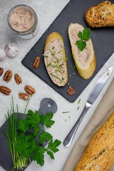 Sanduíches de baguete com patê de carne, bruschettas de carne em uma placa de ardósia preta com ervas, nozes e alho em uma superfície de concreto cinza claro