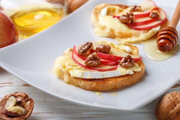 Sanduíches de bruschetta com queijo brie ou camembert, maçãs, nozes e mel