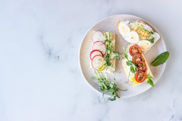 Sanduíches de café da manhã com cream cheese, ovos de codorna, tomate, rabanete e micro verde