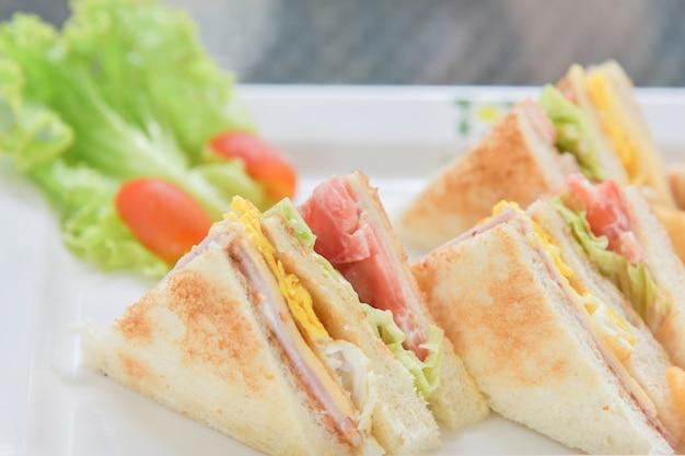 Sanduíches de café da manhã com salada e tomate no prato branco