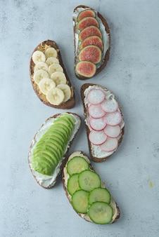 Sanduíches de café da manhã saudável com abacate, pepino, figo, banana, creme de queijo.