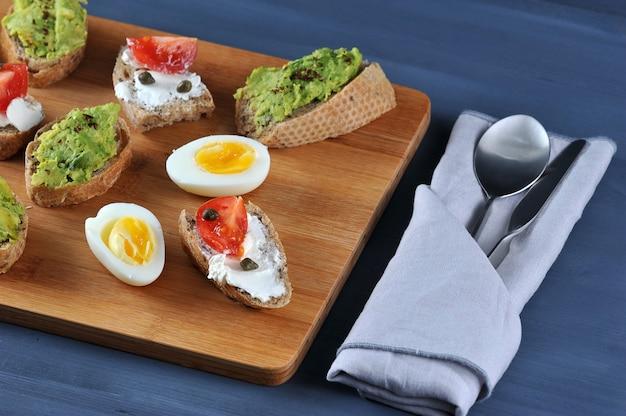 Sanduíches de canapé em uma placa de madeira