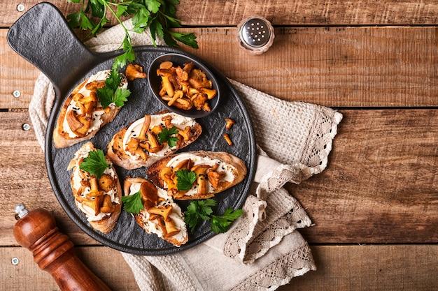 Sanduíches de chanterelle com queijo. sanduíche aberto com queijo cremoso, temperos e pimenta e salsa fresca em um velho fundo de madeira. brincar. vista do topo.