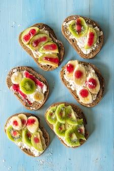 Sanduíches de composição com creme de frutas, banana, maçã e kiwi em um fundo azul de madeira