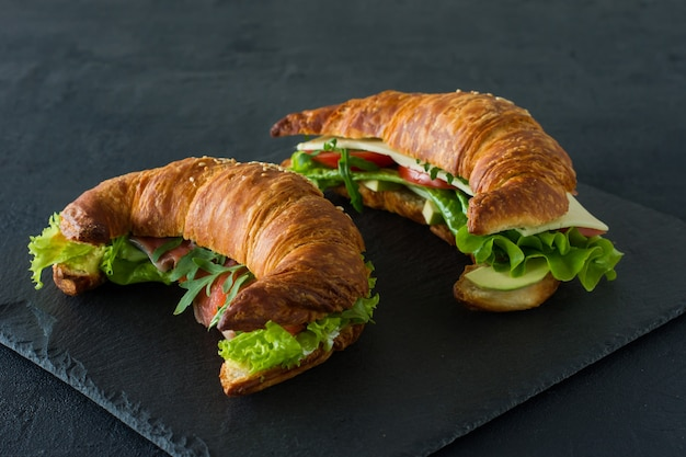 Sanduíches de croissant com salmão salgado em uma mesa, servidos com folhas de salada fresca, rúcula e vegetais sobre fundo preto.