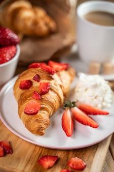 Sanduíches de croissant e xícaras de café na mesa de madeira
