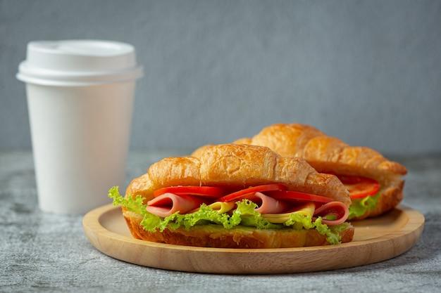 Sanduíches de croissant em superfície de madeira escura