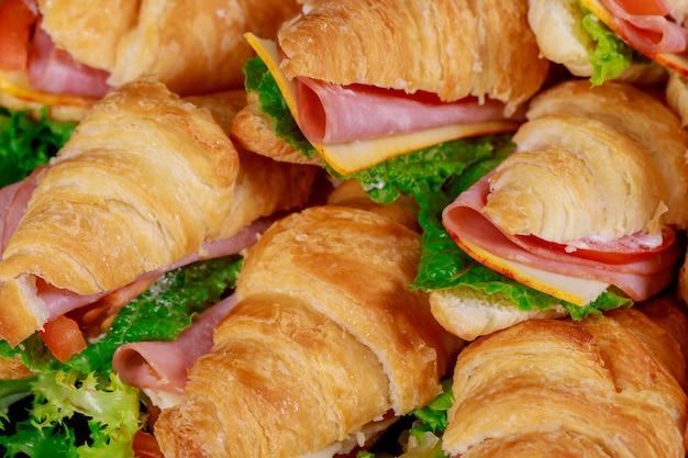 Sanduíches de croissants com alface, queijo, tomate e presunto