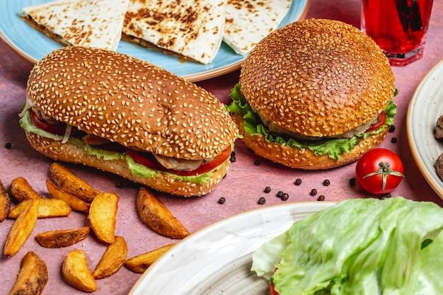 Sanduíches de frango frango tomate pepino alface pãezinhos com vista lateral de gergelim