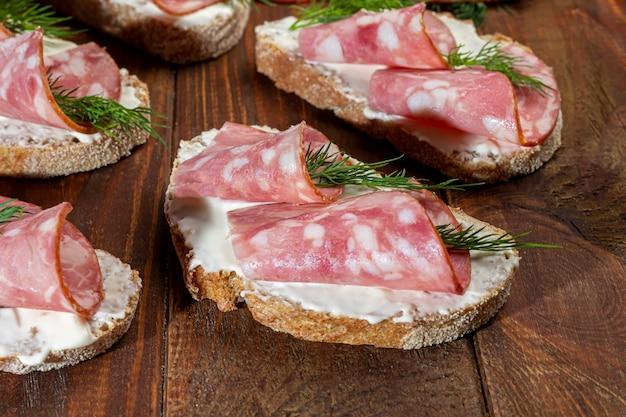 Sanduíches de linguiça defumada e cream cheese. decorado com ervas de endro. sobre um fundo escuro de madeira. copie o espaço.
