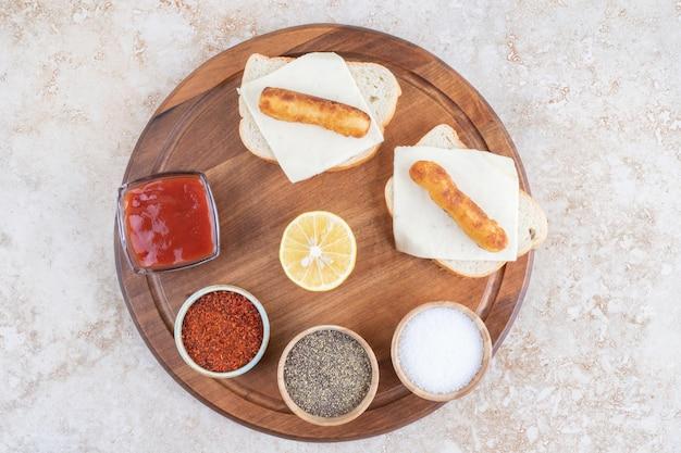 Sanduíches de linguiça grelhada com ketchup em uma placa de madeira.