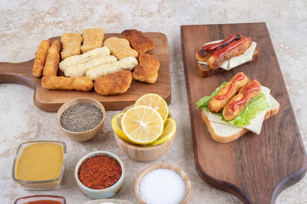 Sanduíches de linguiça grelhada com queijo e nuggets de frango e diversos molhos.