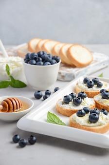 Sanduíches de mirtilo e mel, conceito de café da manhã saudável.