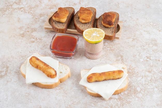 Sanduíches de nugget de frango e linguiça com limão e ketchup.