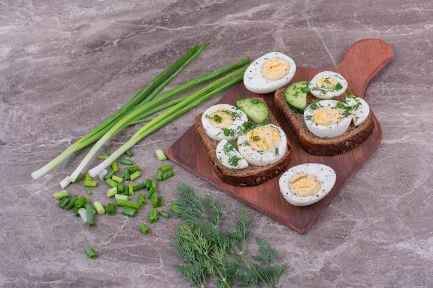 Sanduíches de ovo cozido em uma placa de madeira.