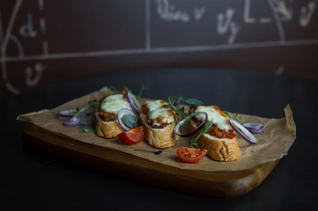 Sanduíches de pão branco com patê de carne com anéis de cebola roxa com rúcula e fatias de tomate vermelho fresco em uma placa de madeira em um restaurante. comida deliciosa e jantar saudável