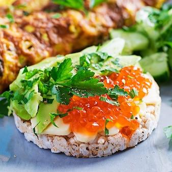 Sanduíches de pão crocante com caviar vermelho, abacate e cream cheese no prato.