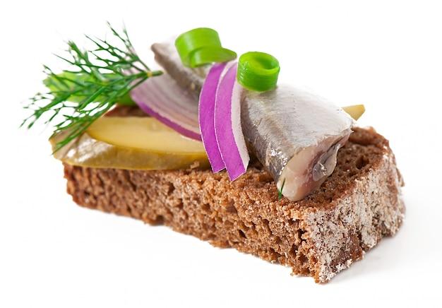 Sanduíches de pão de centeio com arenque, cebola e ervas.