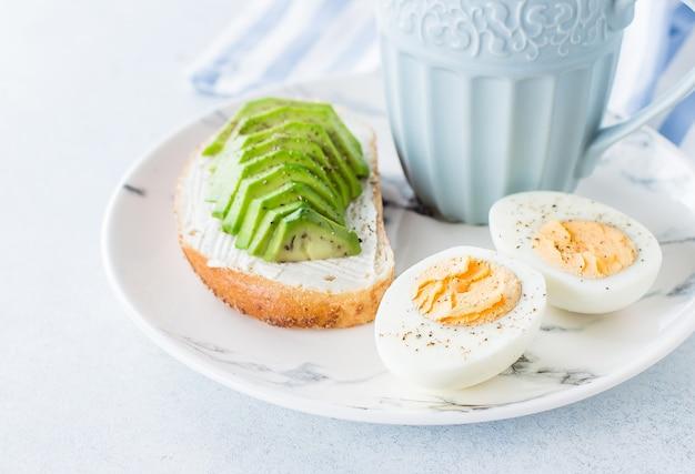 Sanduíches de pão integral com abacate e ovos cozidos na placa de madeira e café
