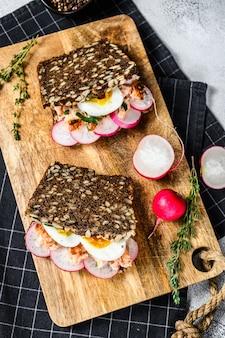 Sanduíches de pão integral com salmão defumado quente, ovos e rabanetes. comida saudável e equilibrada. superfície cinza, vista superior.