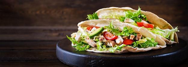 Sanduíches de pão pita com carne de frango grelhado, abacate, tomate, pepino e alface, servidos na mesa de madeira