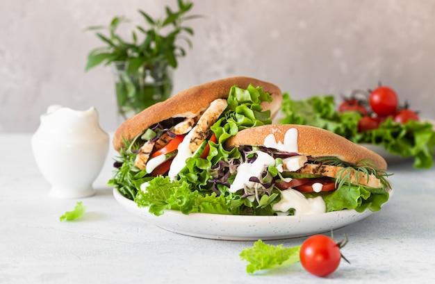 Sanduíches de pão pita com frango, legumes e molho