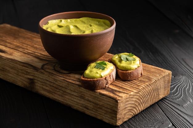 Sanduíches de pão torrado e caviar de abóbora com salsa em fundo de madeira